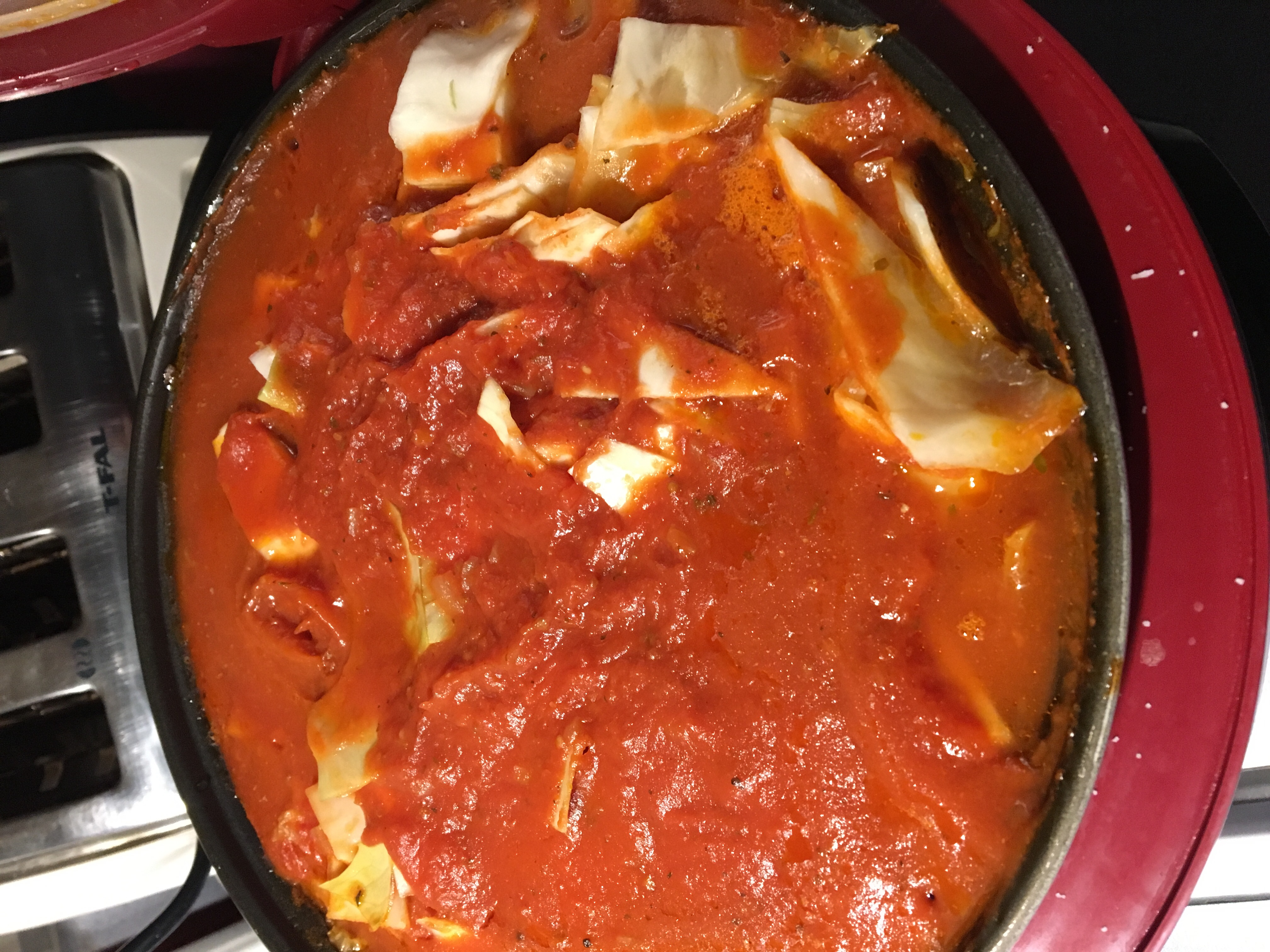 Photo of cabbage roll casserole in a slow rice cooker, but there is cabbage and rice that look raw in the top.