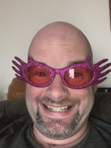 A photo of me in fancy purple and pink glasses my daughter asked me to wear.